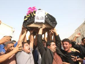 Des hommes transportent le cercueil d'un proche au lendemain du double attentat à Bagdad.