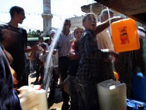 Scène prise dans le village palestinien de Qarawat Bani Zeid, en Cisjordanie, lors d'une distribution d'eau organisée par des ONG israéliennes et étrangères pour protester contre les politiques de Tel-Aviv.