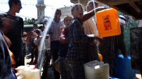 Scène croquée dans le village palestinien de Qarawat Bani Zeid, en Cisjordanie, lors d'une distribution d'eau organisée par des ONG israéliennes et étrangères pour protester contre les politiques de Tel-Aviv.