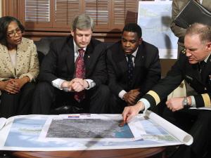 Stephen Harper écoute un exposé du chef d'État-major Walt Natynczyk en compagnie de représentants de la communauté haïtienne.