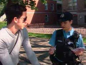 Une policière remet de l'information à un cycliste dans une rue de Montréal.