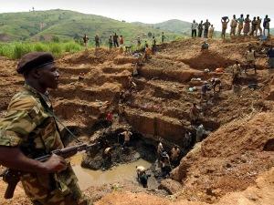 Un combattant de l'Union des patriotes congolais, en Ituri, surveille les travailleurs d'une mine d'or. En RDC, les mines enrichissent davantage les groupes armées et les compagnies étrangères que les Congolais.