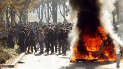Des jeunes se tiennent devant un véhicule incendié à Nanterre, près de Paris.