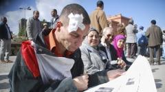 Un manifestant blessé lit le journal au Caire.