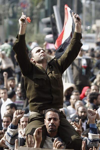 Un homme portant un uniforme de capitaine de l'armée égyptienne est porté par la foule rassemblée lundi place Tahrir.