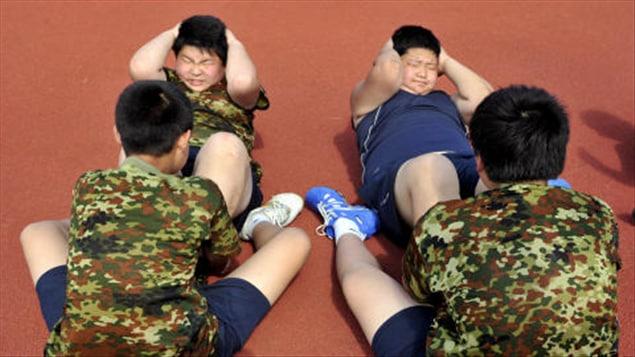 Des enfants obèses chinois peinent à faire des redressements assis.