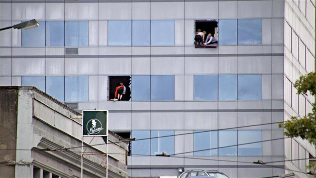 Des employés brisent des fenêtres pour accueillir les secours qui viendront en échelles.
