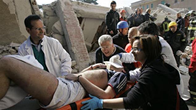 Des secouristes sortent un homme vivant des décombres, dans la ville de L'Aquila, le 6 avril 2009.