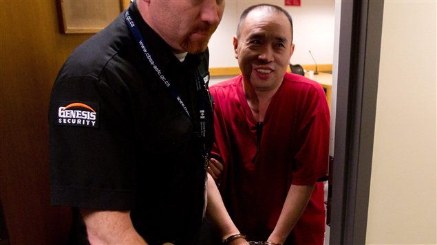 Un gardien escorte Lai Changxing, à Vancouver, le 11 juillet 2011.