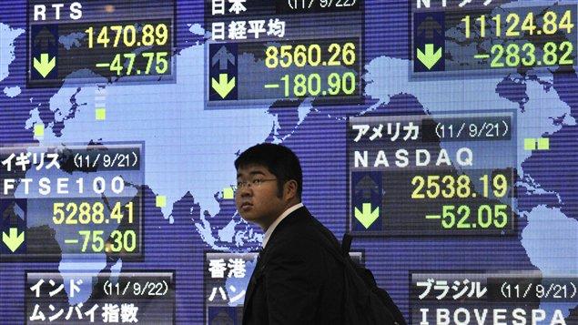 Un Japonais devant un tableau illustrant la chute des places boursières.