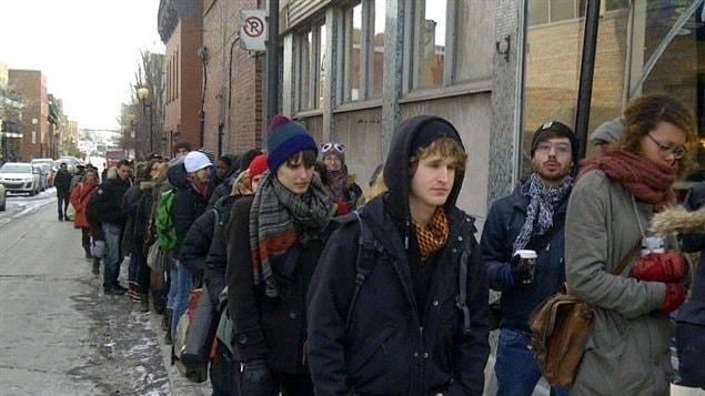 Des étudiants en art de l'UQAM attendent en file devant Le National sur la rue Ste-Catherine à Montréal pour voter à l'assemblée général de déclenchement de grève.