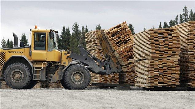 Un homme transporte du bois à Armstrong, au Québec