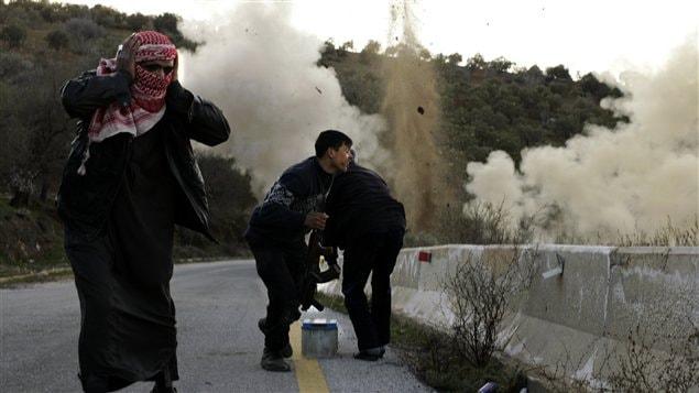 Des rebelles posent une bombe dans la province d'Idlib afin de bloquer l'accès aux régions montagneuses du nord de la Syrie, le 20 mars 2012.