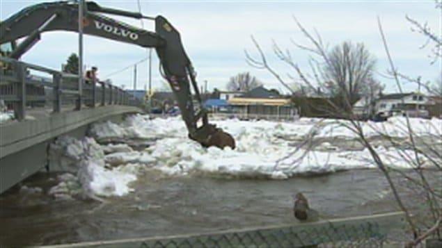 Travaux d'une excavatrice pour dégager une partie des glaces accumulées