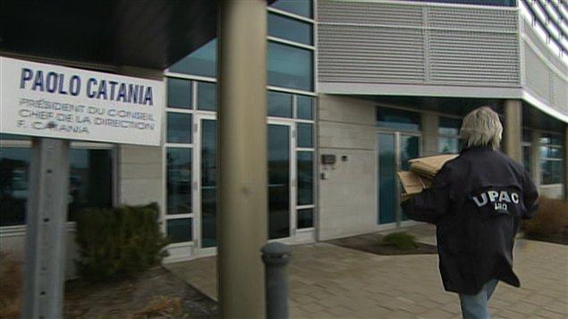 Un enquêteur de l'UPAC transporte des boîtes de carton sur les lieux de la perquisition.