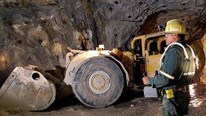 Un ouvrier et de l'équipement lourd dans une mine d'uranium de Cameco