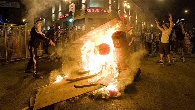 Des manifestants brûlent des barricades et des cônes de signalisation routière au centre-ville de Montréal.