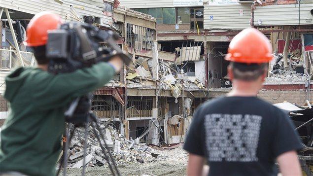 Des ouvriers filment les dommages sur le site de l'effondrement à Elliot Lake.