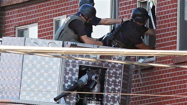 Des policiers inspectent l'appartement du suspect depuis la nacelle d'un camion de pompier.