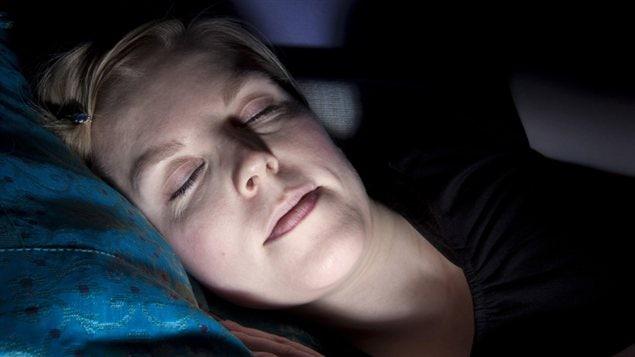 Une femme dort devant la télévision.