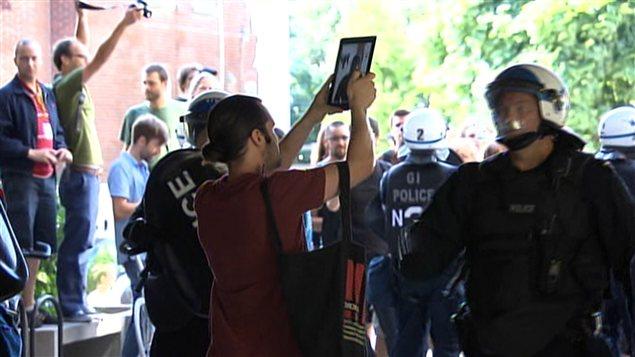 Un étudiant qui prend des photos des policiers sur le point d'être interpellé.