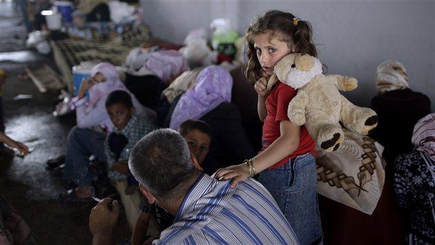 Une fillette syrienne, qui a fui Marea avec sa famille, attend dans un refuge au poste frontalier Bab Al-Salameh. (29 août 2012)
