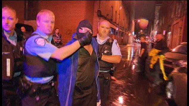 Un agent du SPVM remonte la cagoule du suspect sur son visage pendant que ce denrier vocifère des propos incompréhensibles aux journalistes.