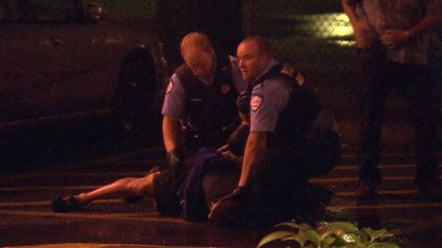 Des agents du SPVM menottent le suspect plaqué au sol à la suite de son arrestation.