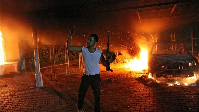 Un homme armé montre son arme alors que le consulat américain brûle à Benghazi, le 11 septembre 2012.