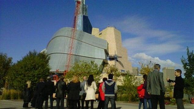 La dernière pièce de verre sur le point d'être posée sur l'édifice du Musée canadien pour les droits de la personne.