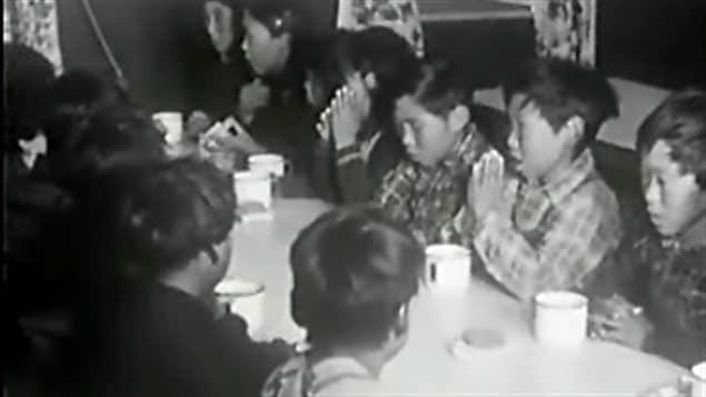 Des élèves d'un pensionnat autochtone au Canada font une prière avant leur repas.