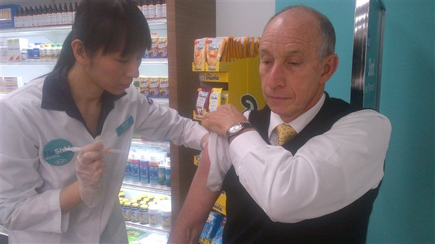 Un Torontois se fait vacciner contre la grippe dans une pharmacie.