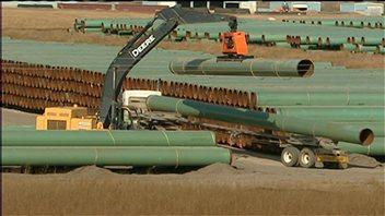 Une grue lève un tuyau de pipeline.