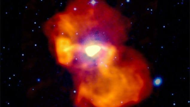 L'Image en fausses couleurs de la galaxie M 87. La lumière visible apparaît en blanc et bleu. L'émission radio est codée en jaune-orangé. Au centre, l'émission radio très intense provient du jets de particules propulsé par le trou noir.