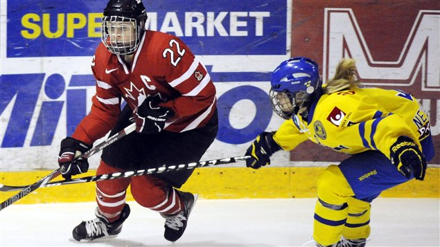 La Canadienne Hayley Wickenheiser (22) et la Suédoise Frida Nevalainen en action dans un match de la Coupe des 4 nations remporté 9-0 par le Canada.