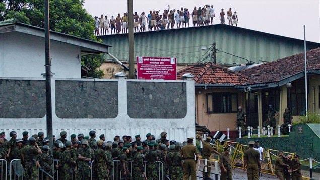 Des prisonniers sri-lankais narguent les policiers restés au sol, lors d'une émeute survenue dans une prison de la Colombo
