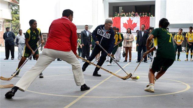 Le premier ministre Stephen Harper dispute un match de hockey en Inde.