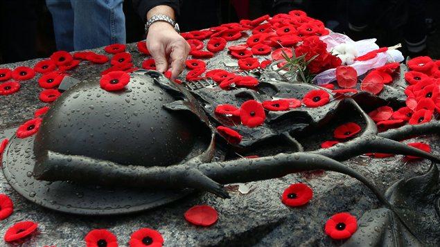 Des Canadiens déposent leur coquelicot sur la tombe du soldat inconnu à Ottawa.