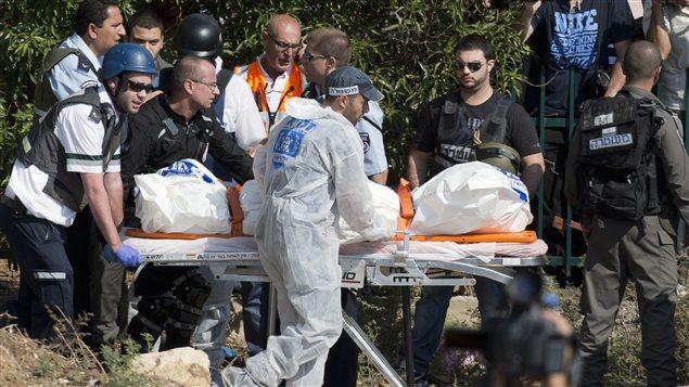 Des secouristes israéliens évacuent le corps d'une des trois victimes d'un tir de roquette en provenance de la Palestine.