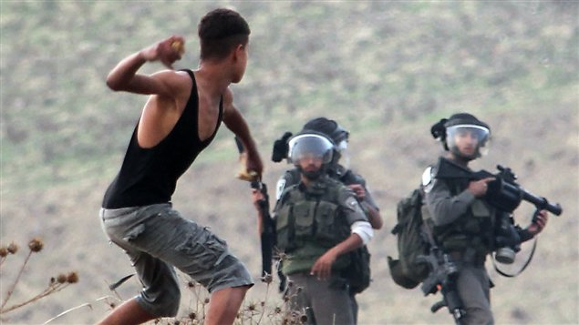 Un jeune Palestinien tire une roche aux soldats israéliens le 18 novembre 2012.