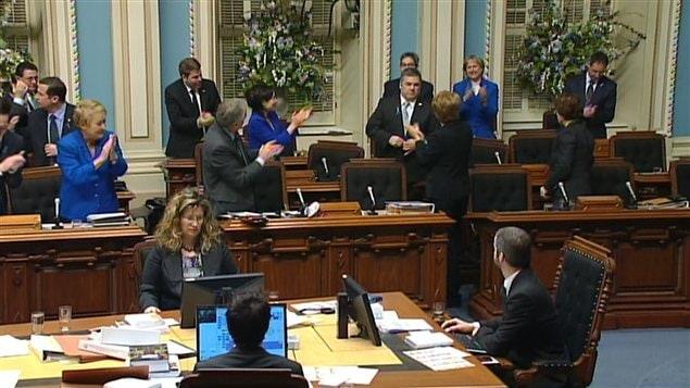 Les députés du gouvernement péquiste saluent leur collègue Daniel Breton. (à droite)