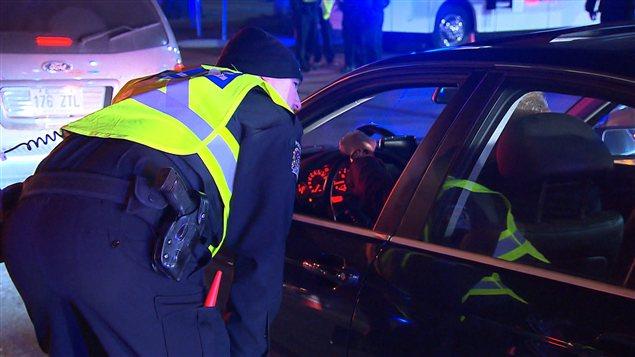 Un policier questionne un automobiliste lors de d'un barrage routier, jeudi soir, au sud de Montréal.