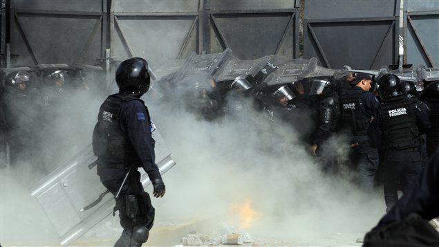 Des policiers antiémeute tentent d'empêcher des manifestants de mettre à terre une clôture de sécurité à l'extérieur du Parlement lors de l'assermentation du président.