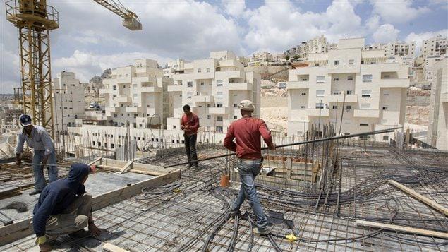 Des travailleurs érigent un complexe d'habitation à Jerusalem-Est.