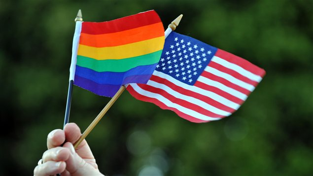 Un homme gai brandit un drapeau de la fierté gai et un drapeau américain lors d'une manifestation en 2008, à Hollywood.