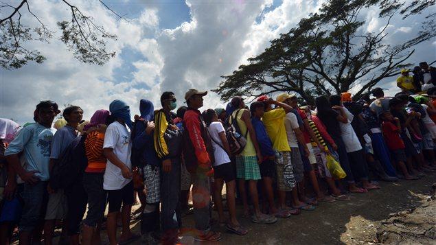 Des Philippins sinistrés après le passage du typhon faisaient la queue pour avoir dela nourriture, dimanche, dans le sud du pays.