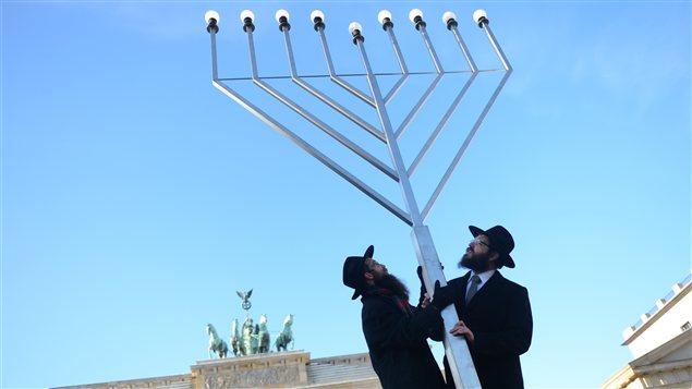 Des rabbins érigent une menorah, un chandelier à sept branches qui représente un emblème biblique.