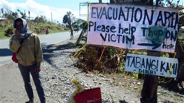 Un Philippin attend devant une affiche qui annonce un centre d'accueil pour les sinistrés du typhon Bopha