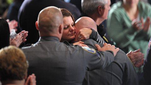 Une femme réconforte un membre du corps de police de Newtown quelques minutes avant que Barack Obama ne prononce son discours lors de la cérémonie religieuse.
