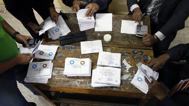 Des officiels procèdent au décompte des bulletins de vote, après le premier jour de vote sur le projet de Constitution en Égypte